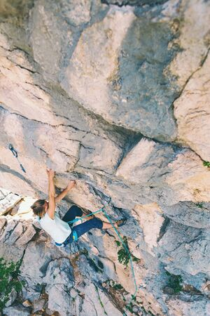 Climber overcomes challenging climbing route. A girl climbs a rock. Woman engaged in extreme sport. Extreme hobby. Foto de archivo - 127584846