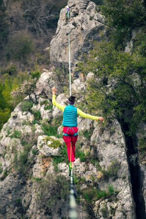 A woman is walking along a stretched sling. Highline in the mountains. Woman catches balance. Performance of a tightrope walker in nature. Foto de archivo - 127584880