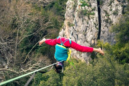 girl falls on a stretched sling. Highline in the mountains. woman lost her balance. Speech tightrope walker in nature. Highliner hanging on a rope. Fall athlete. Foto de archivo - 127584934