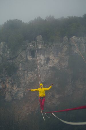 Highline in the fog. Highliner on the background of the rock. A woman catches the balance on a stretched sling. Rope walker in the haze. Foto de archivo - 127586120
