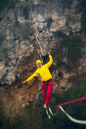 Highline in the fog. Highliner on the background of the rock. A woman catches the balance on a stretched sling. Rope walker in the haze. Foto de archivo - 127586126