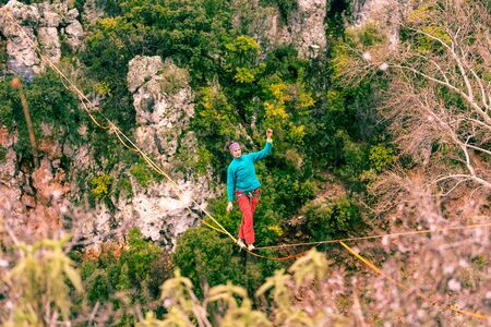A woman is walking along a stretched sling. Highline in the mountains. Woman catches balance. Performance of a tightrope walker in nature. Foto de archivo - 127586131