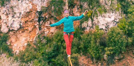A woman is walking along a stretched sling. Highline in the mountains. Woman catches balance. Performance of a tightrope walker in nature. Foto de archivo - 127586135