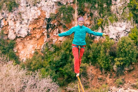 A woman is walking along a stretched sling. Highline in the mountains. Woman catches balance. Performance of a tightrope walker in nature. Foto de archivo - 127586141