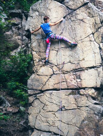 The girl climbs the granite rock. Rock climber trains on natural terrain. Extreme hobby. Foto de archivo - 127586295