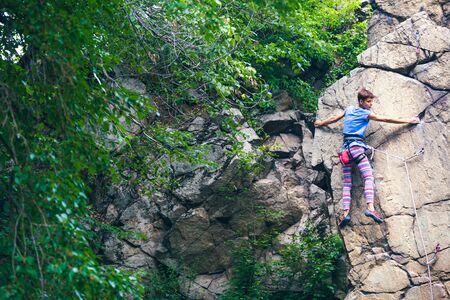 The girl climbs the granite rock. Rock climber trains on natural terrain. Extreme hobby. Foto de archivo - 127586296