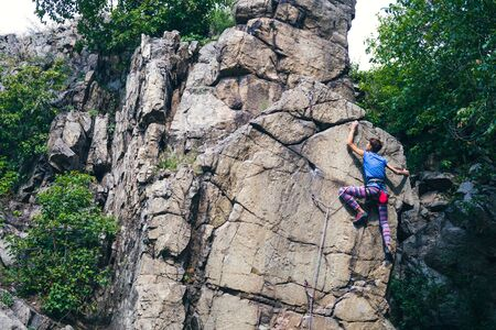 The girl climbs the granite rock. Rock climber trains on natural terrain. Extreme hobby. Foto de archivo - 127586298