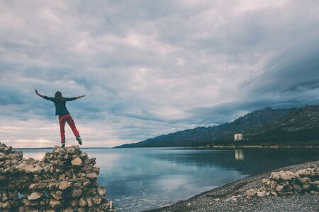 The girl stands on a pile of stones and looks at the sea. Woman catches balance on the stone. Tourist explores the sights of Croatia. Female silhouette against the sunset sky. 스톡 콘텐츠