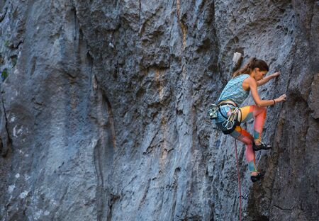 Climber overcomes challenging climbing route. A girl climbs a rock. Woman engaged in extreme sport. Extreme hobby.