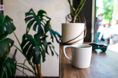 Americano in a white cup. Coffee mug on a wooden table. Morning refreshing drink. Stok Fotoğraf