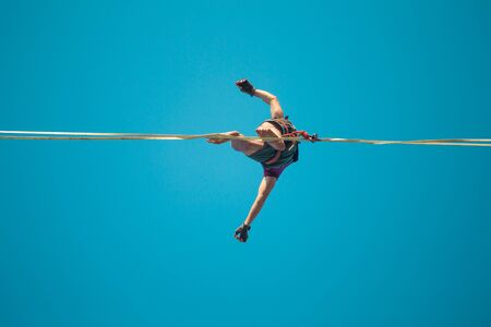 Highliner on the background of blue sky makes a move. A man is walking along a stretched sling view from below. Performance tightrope walker. Man balances over the abyss. A decisive step forward.
