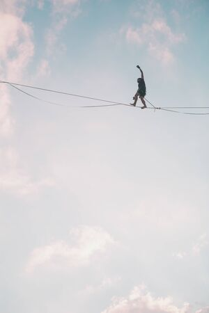 Highliner on the background of blue sky makes a move. A man is walking along a stretched sling. Performance tightrope walker. Man balances over the abyss. A decisive step forward.