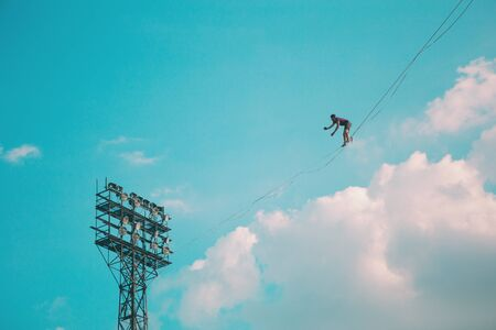 Highliner on a background of blue sky. A man walks along a sling stretched between the towers. The performance of the tightrope walker. A man is balancing over a precipice. A decisive step forward.