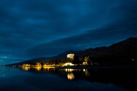 Lighting night resort town. Sunset on the sea coast. Calm night sea. Coast of Croatia.