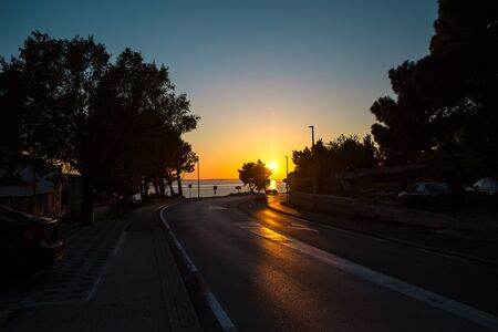The road to the sea against the sunset sky. Road on the Adriatic coast. The setting sun. The track along the sea.