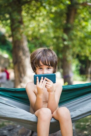 A child sits in a hammock and looks into a smartphone. A boy is playing on the phone. A child reads while resting. Stok Fotoğraf