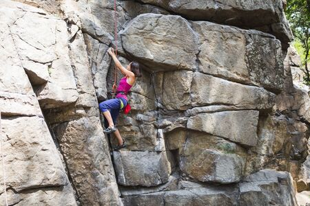 The girl climbs the rock. Rock climber is training on natural terrain. Extreme hobby. A woman overcomes a difficult climbing route. Stock Photo