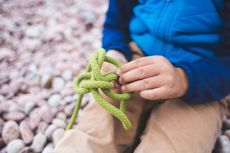 A child learns to knit a knot from a rope. A little boy is trying to tie a knot. Scout training. Children's hands and safety rope. Stock Photo