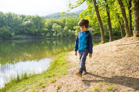 Ein Kind am See. Ein Junge mit Rucksack steht am Ufer des Flusses. Das Kind geht durch den Wald. Gehen Sie an einem sonnigen Frühlingstag im Park spazieren. Der Junge schaut auf das Wasser. Standard-Bild