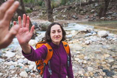 Girl greets friend. A woman with a friend is walking in the woods. The couple travels to scenic places. The girl gives five. Gesture of greeting. A tourist crosses a mountain river to a ford. Stok Fotoğraf