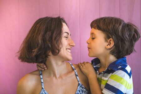 Cute boy kisses and hugs mom. Portrait of a woman with a child. The brown-eyed boy whispers to mom in the ear. Stok Fotoğraf