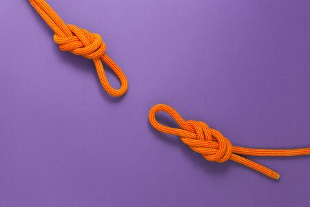 Orange climbing rope on a purple background. Safety knot. Two knots the eight for safety. Stok Fotoğraf