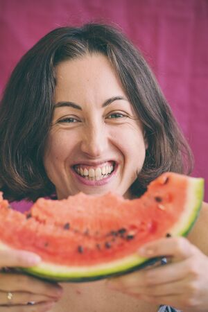 A woman eats a watermelon and laughs. Girl eats juicy watermelon and smiles.