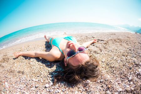 girl lying on the sand near the sea. holidays on the ocean coast. A young woman in glasses and a swimsuit with a holbait is lying on the sand near the water.