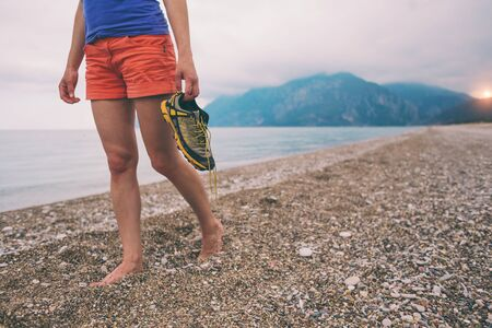A woman took off her shoes and walks along the sandy beach. The girl carries sneakers in her hands and goes along the seashore. Barefoot woman on the background of the ocean and overcast sky. Standard-Bild - 129101193