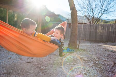 Kids are played in a hammock. Boys spend time in the fresh air. Summer holiday in nature. Children lie in a hammock near a wooden house.