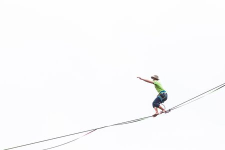 Highliner on a white background makes a move. A man is walking along a stretched sling. Performance tightrope walker. Man balances over the abyss. A decisive step forward.