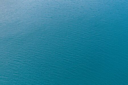 Background shot of aqua sea water surface. Water background with blue peaceful ripples for use as texture or background. Stock fotó