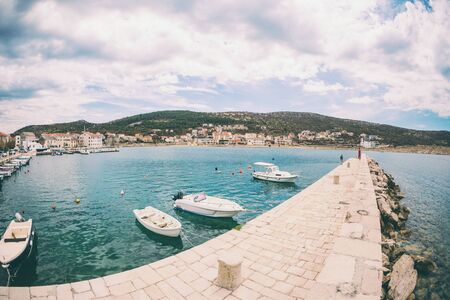 Motor boats on the pier. Sea coast of Croatia. Swimming facilities by the sea. Yachts and sailboats in the port. Fishing boats.