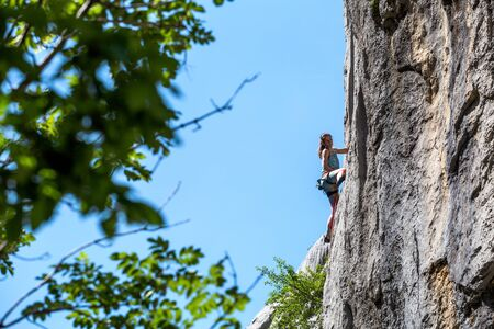 Rock climbing and mountaineering in the Paklenica National Park. A woman overcomes a challenging climbing route on natural terrain. Climber trains on the rocks of Croatia. Stock Photo