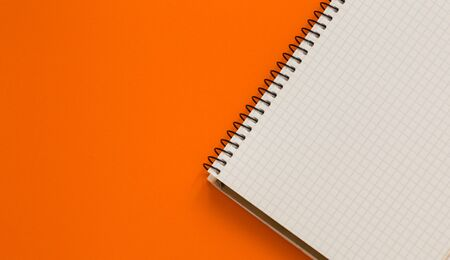 Notepad on an orange background. Open notebook. Checkered sheet in notebook.