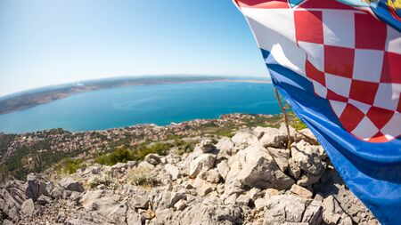 flag waving in the wind. Croatia flag mounted on the top of the mountain. Fish lens.