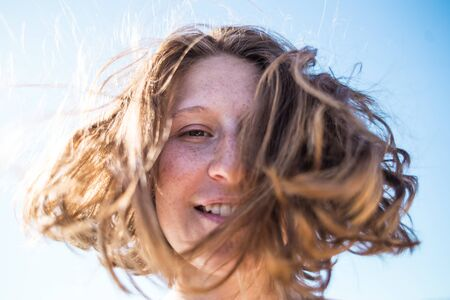 portrait of a girl with freckles on her face. hair that spills in the wind. beautiful and happy.
