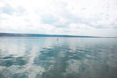 Young attractive woman kayaking, SUP, in the blue waters of the sea. a lonely girl stands on a board in the middle of a strait in the Adriatic Sea of Croatia. active life concept. Stock fotó
