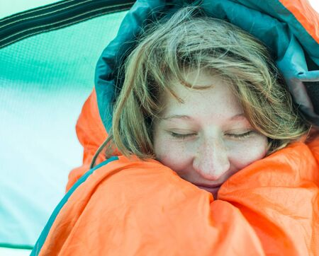 Portrait of a girl with freckles who laughs while sitting in a sleeping bag. Fun pastime and outdoor recreation. beautiful girl in a sleeping bag.