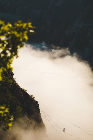 a man walks along a stretched sling high above the clouds. highliner catches the balance on a long and high sling pull in a canyon. Extreme sports in Bosnia and Herzagovina, Stock Photo