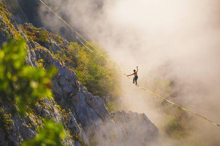 un homme marche le long d'une fronde tendue au-dessus des nuages. highliner trouve l'équilibre sur une longue et haute traction dans un canyon. Sports extrêmes en Bosnie-Herzégovine, Banque d'images