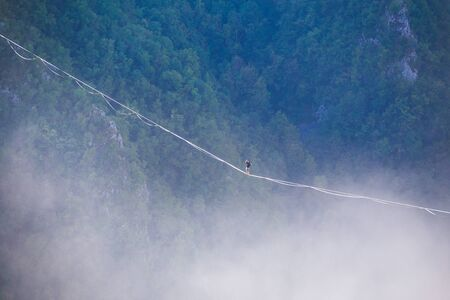 a man walks along a stretched sling high above the clouds. highliner catches the balance on a long and high sling pull in a canyon. Extreme sports in Bosnia and Herzagovina, Stock fotó