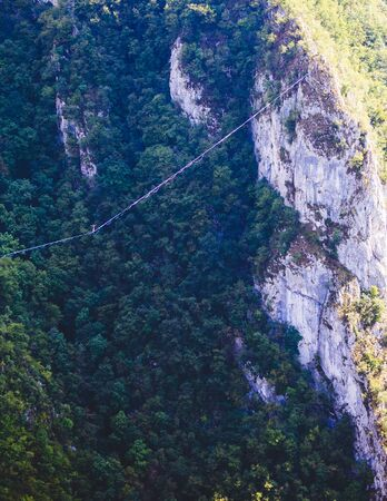 Highline in the mountains. A man goes on a stretched sling. Highline is on the line. A tightrope walker catches balance. Equilibrium. Confidence in a tense situation.