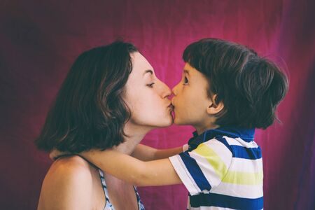 Cute boy kisses and hugs mom. Portrait of a woman with a child. The brown-eyed boy whispers to mom in the ear. Stock fotó