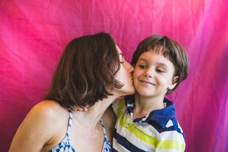 Cute boy kisses and hugs mom. Portrait of a woman with a child. A woman hugs her son. Stock fotó