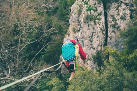 girl falls on a stretched sling. Highline in the mountains. woman lost her balance. Speech tightrope walker in nature. Highliner hanging on a rope. Fall athlete.