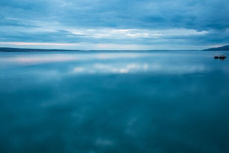 Sea coast of Croatia. Sea and sky with clouds. Calm water. Evening and sunset sun. Stock fotó