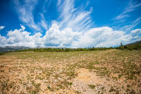 Earth and beautiful sky with clouds. Dry soil. Rocky ground and mountains. Stock fotó