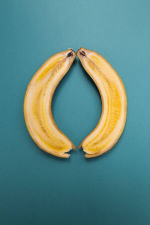 Banana cut along. Two halves of a banana on a blue background. Ripe fruit.
