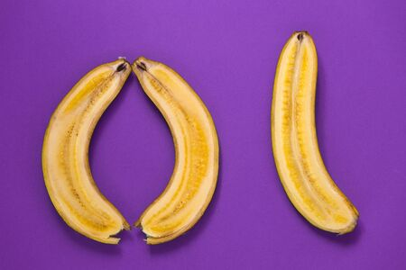 Banana cut along. Three halves of a banana on a purple background. Ripe fruit. Circle of cut fruit. Stock fotó